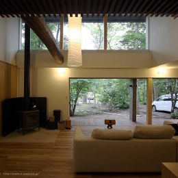 林の中の水平(軽井沢の別荘) (ウッドデッキテラスと繋がる暖炉のあるリビング)
