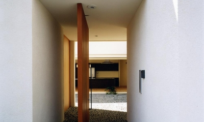 中庭と水盤のある家|上新田の家 (木製回転扉より中庭と4mステンレスキッチンを見る 砕石の洗い出し土間)