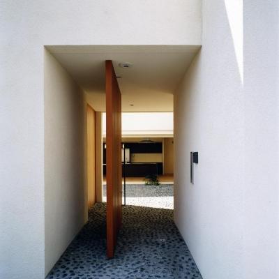 木製回転扉より中庭と4mステンレスキッチンを見る 砕石の洗い出し土間 (中庭と水盤のある家|上新田の家)