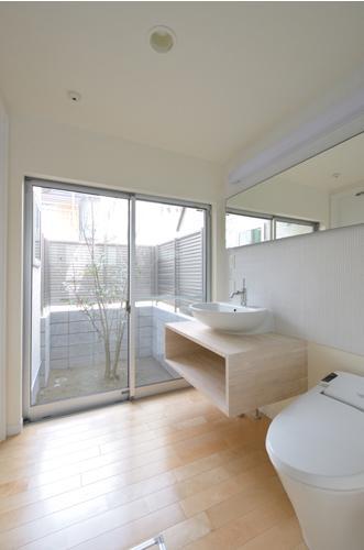 樹の庭がある家の部屋 庭を感じるトイレ・洗面