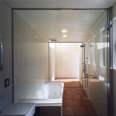 テラコッタのルーフテラスに繋がる ガラス張りバスルーム (中庭と水盤のある家|上新田の家)