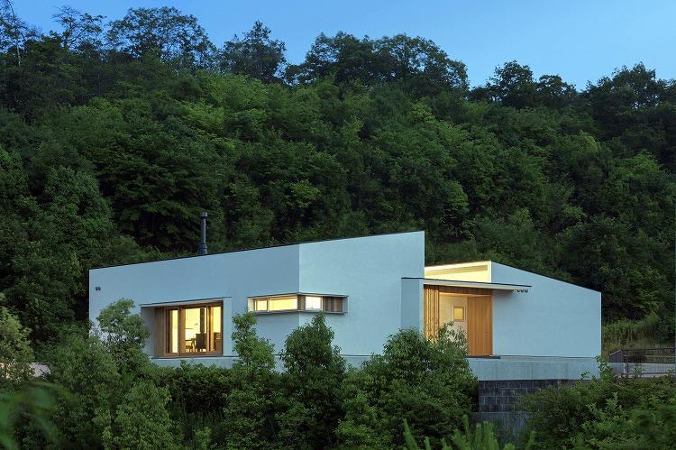喜多町の家の部屋 緑に囲まれた白い外観 (夕景)