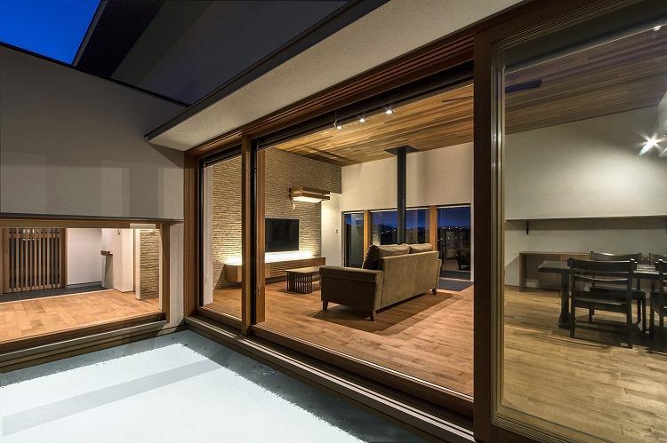喜多町の家の部屋 中庭から明かりの灯ったLDKを望む