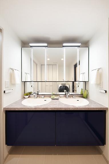 住空間にサロンをもつという選択 (鏡面仕上げの青い扉が美しい2ボウルの洗面台)