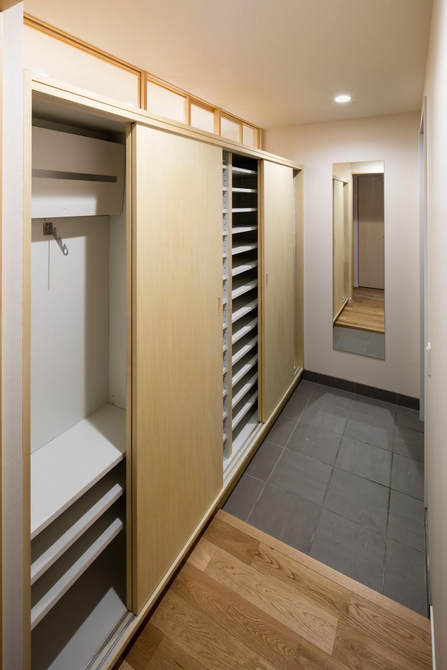 ルーフバルコニーを生かす広いリビングと開放性のある心地よいパウダールームのある家の部屋 棚の位置を変えられる玄関収納