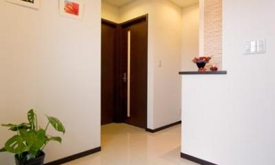 自然に家族とのコミュニケーションが取れる家 (黒いタイルと白い大理石でメリハリをつけた玄関)