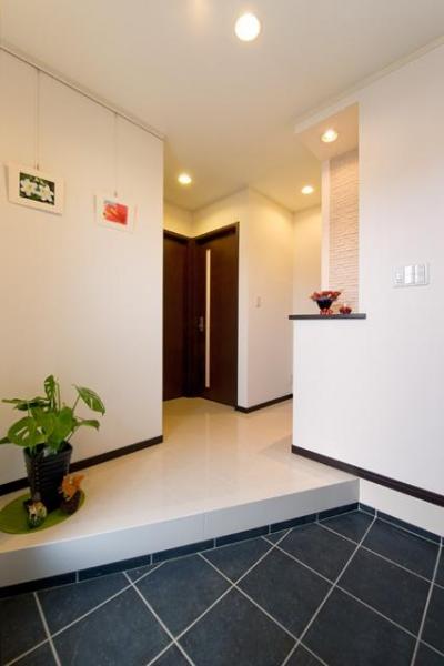 黒いタイルと白い大理石でメリハリをつけた玄関 (自然に家族とのコミュニケーションが取れる家)