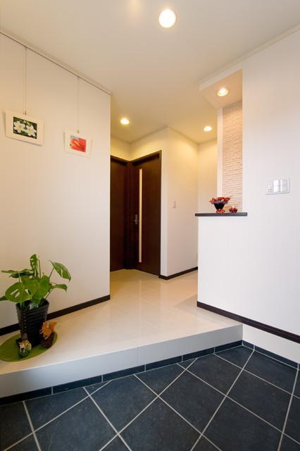 自然に家族とのコミュニケーションが取れる家の部屋 黒いタイルと白い大理石でメリハリをつけた玄関