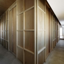 合板の壁で囲われた部屋とL字形の土間空間