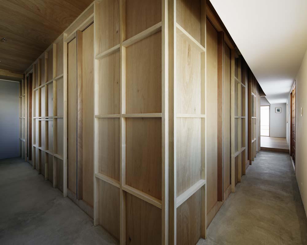 玄関事例:合板の壁で囲われた部屋とL字形の土間空間(囲みの層)