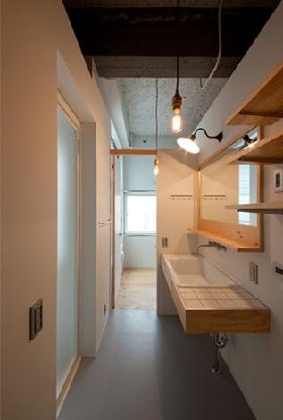 マトリョーシカノイエの部屋 収納棚のある白いタイルの洗面室