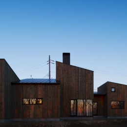 CNAN (5つの片流れ屋根で構成された外観-夕景)