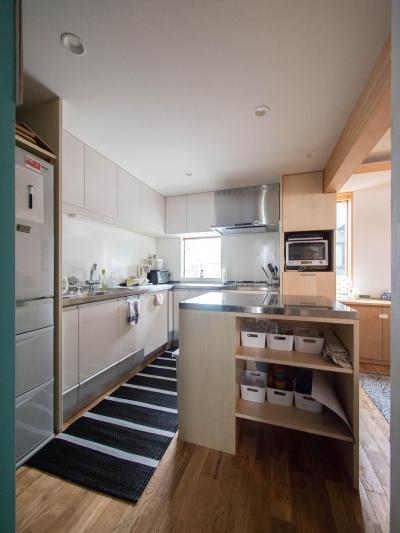 L型キッチンとアイランド型の作業台 (三層回遊の家)