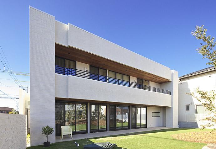 タイルと土とアートと暮らす家の部屋 庭と隣接するリビングを持つ家