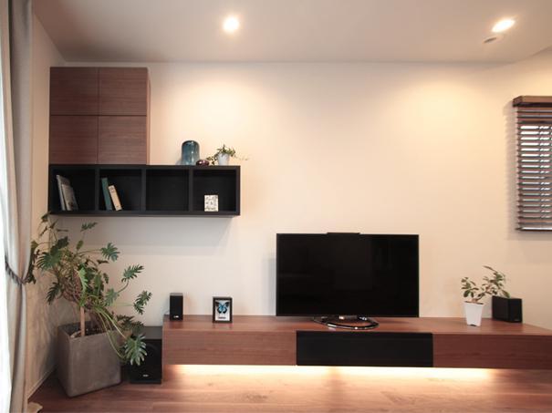 家族が集まる寛ぎのリビングの部屋 無垢材の床やテーブルに合わせた造作家具の吊棚とテレビボード