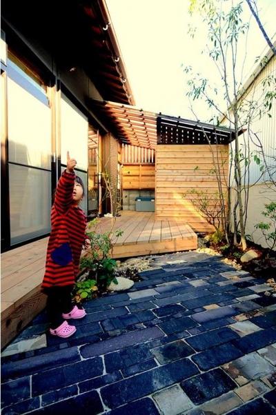 石畳のある庭とウッドデッキテラス (心地よい 『いつも一緒』 なリビング)