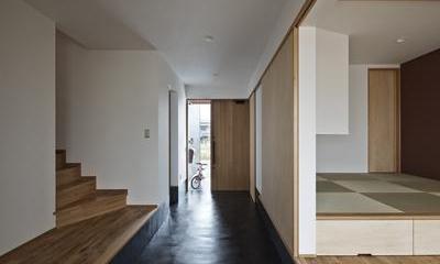 建築の中にある通り土間に向い合って住まう2世帯住宅インナーバイクガレージと趣味室 : 木津川の住宅