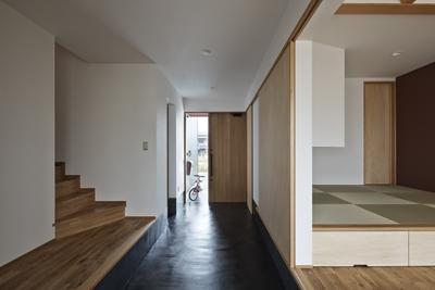 建築の中にある通り土間に向い合って住まう2世帯住宅インナーバイクガレージと趣味室 : 木津川の住宅 (全体を眺める)