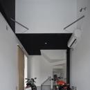 建築の中にある通り土間に向い合って住まう2世帯住宅インナーバイクガレージと趣味室 : 木津川の住宅の写真 吹き抜け空間とバイクガレージ
