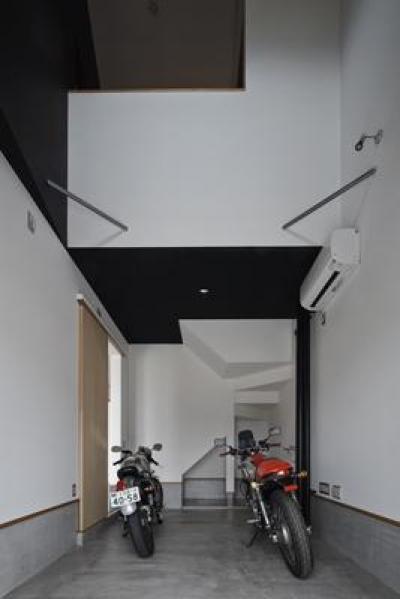 建築の中にある通り土間に向い合って住まう2世帯住宅インナーバイクガレージと趣味室 : 木津川の住宅 (吹き抜け空間とバイクガレージ)