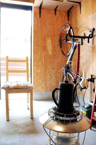アウトドア用品やバイクなどが並ぶガレージ (渋谷区E様邸 鉄骨階段とガレージのある家)