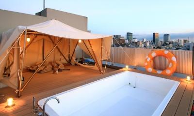 マンション最上階のルーフテラスで都心の眺めを楽しむテント&展望プール (ルーフテラスのテント&プール:夕方)