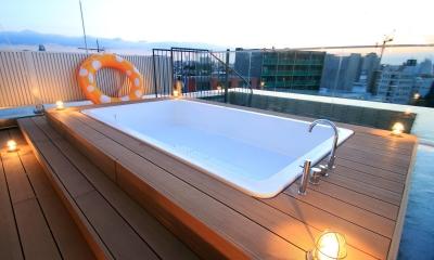 マンション最上階のルーフテラスで都心の眺めを楽しむテント&展望プール (ウッドデッキプールと上向き照明)