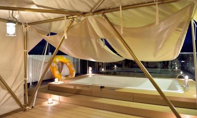 マンション最上階のルーフテラスで都心の眺めを楽しむテント&展望プール (明るさ十分の夜間テント内部)