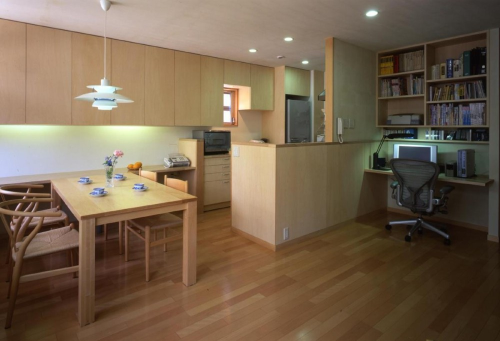 下町で静かに暮らす熟年夫婦の家 (食卓の右奥が、半分隠れたキッチン。 その突き当たりにポストの受け口があります。  キッチンと壁一枚でご主人の書斎コーナーです。)