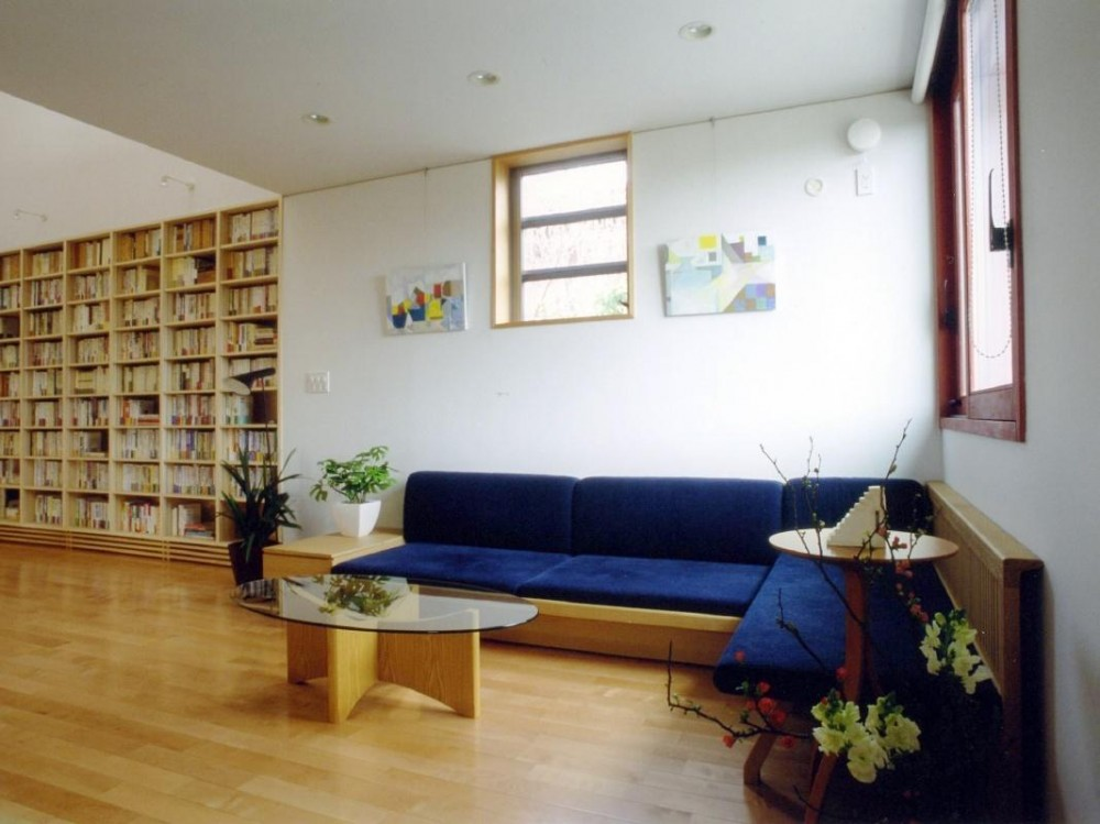 本棚に囲まれた一室空間の家 (コーナーにしつらえられた落ち着いたソファーコーナーです。)