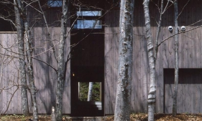 森の中の静かな別荘 (駐車場から階段を登って行きますと、建物の下を通り抜けて前庭にたどりつきます。)