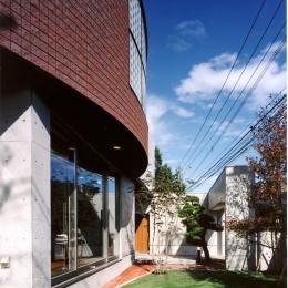 2階オープンテラスのある、焼きすぎレンガタイルの家 I邸 (大きな曲面は2階オープンテラスの目隠し)