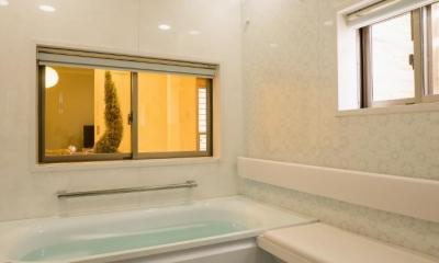 玄関ホールの坪庭に明るい光が降り注ぐ開放的な住まい (浴室)