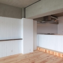 LDKと個室がゆるやかにつながるリラックス空間の写真 パインフローリングと白いアイランドキッチンが印象的なLDK
