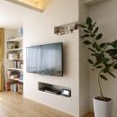 人を招いて楽しい、オープンキッチンとゲスト用食器棚のあるリビングの写真 壁付けテレビ