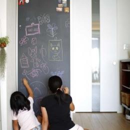 人を招いて楽しい、オープンキッチンとゲスト用食器棚のあるリビングの部屋 黒板壁