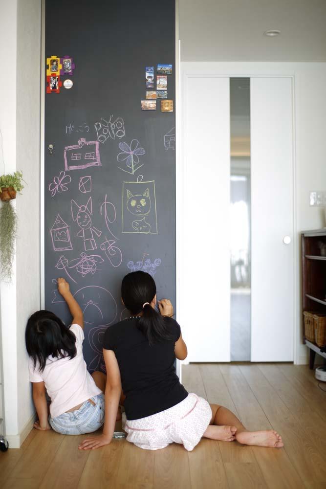 人を招いて楽しい、オープンキッチンとゲスト用食器棚のあるリビング (黒板壁)
