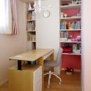 人を招いて楽しい、オープンキッチンとゲスト用食器棚のあるリビングの写真 子ども室デスク