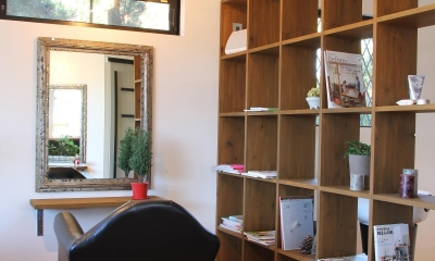 仕切り壁も兼ねた備え付けの本棚|素材感を前面に押し出したヘアサロン兼住宅