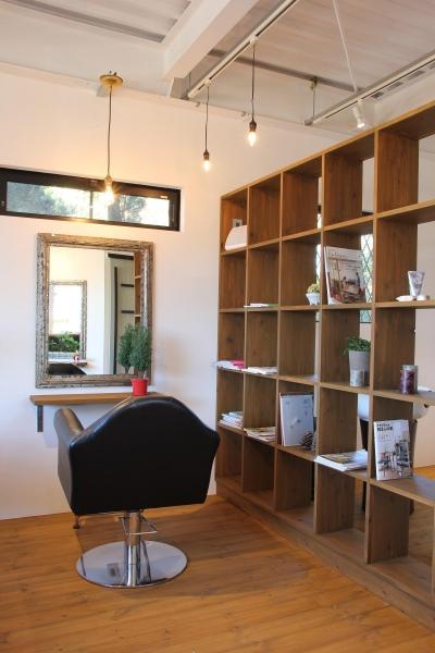 仕切り壁も兼ねた備え付けの本棚 (素材感を前面に押し出したヘアサロン兼住宅)