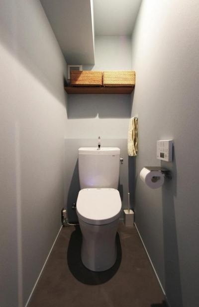 清潔感のあるモルタル仕上げのトイレ (黒とパステル)