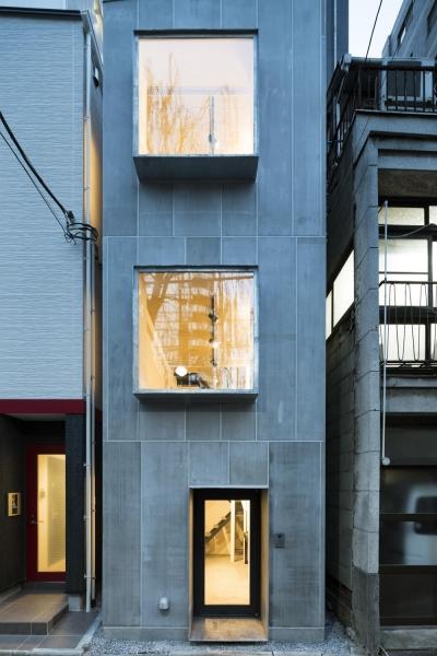蔵前の小さな家 (外観正面夕景 室内の風景が出窓に切り取られて外部に表れる)