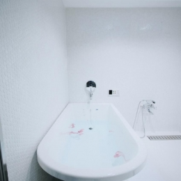 アーバンライフを楽しむマンションリノベーション (白で統一された清潔感あふれるバスルーム)