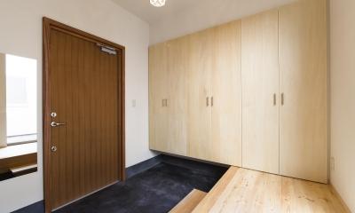 木製ドアと墨色土間ある玄関|今戸コートハウス