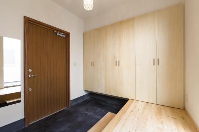 木製ドアと墨色土間ある玄関 (今戸コートハウス)