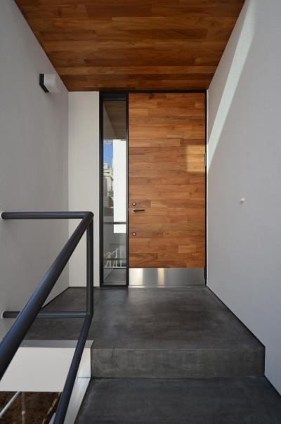 チークの床材を張った玄関扉 (青葉台KM邸-都市公園の緑を借景とするスキップフロアの二世帯住宅-)