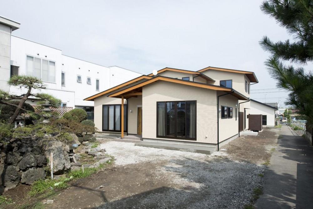 吹抜けと中庭のある家 (木を魅せて積層する屋根の外観)