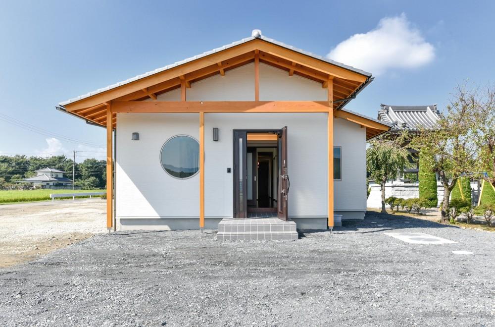 書斎やスタディーのある瓦屋根の家 (木を魅せた丸窓がアクセントの外観)