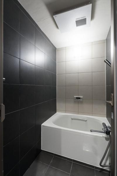 浴室 (石張り壁のあるフルリノベーション:『品川区五反田のリノベーション』)