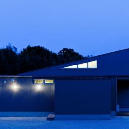 農村風景を望む母屋と並ぶ家 (三角形のハイサイドライトがアクセントの夕景)
